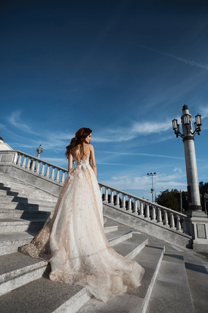 Beautiful model woman with perfect body in luxury wedding dress stands with back on the stairs and posing with blue sky at background