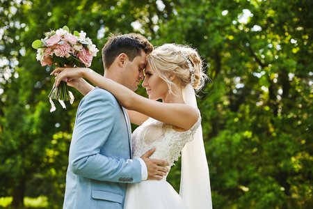 Beautiful blonde model woman with luxury jewelry in her wedding hairstyle and in fashionable dress hugs her handsome groom in the stylish blue blazer and posing outdoors