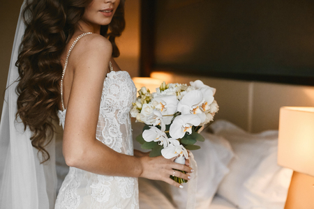 Young brunette woman with wedding hairstyle in a lace wedding dress with a bouquet of fresh flowers in her hands in stylish interior