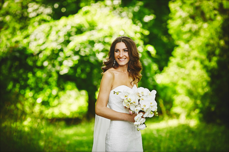 Beautiful brunette young woman with wedding hairstyle in a stylish wedding dress with a white orchid in her hands posing at nature