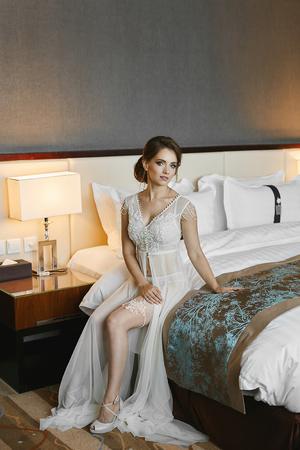 Hermosa mujer morena, con peinado de novia y cuerpo perfecto con piernas largas, en elegante bata y en lencería de encaje posando en la cama en el interior de lujo