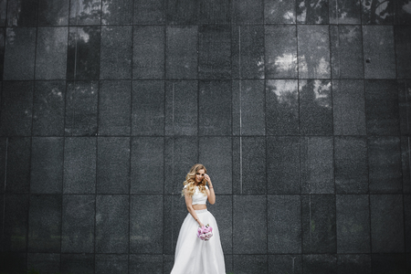 Young and beautiful blonde woman with bouquet of flowers in her hand in a stylish blouse and in tulle skirt posing outdoors in front of the black granite wall