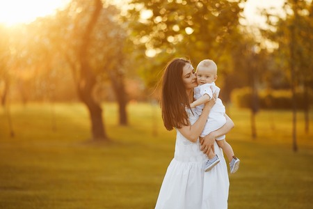 Beautiful young woman in a long white dress with a cute little baby boy in shirt and shorts on her hands posing at the green garden in sunny summer day Stockfoto