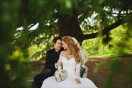 Beautiful couple of just married, young blonde woman in the wedding dress and handsome stylish man in stylish tuxedo sits on a bench under the big tree