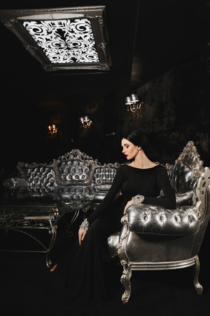Fashionable and brunette model woman with perfect body and with red lips in black evening dress with sits on the silver sofa at modern luxury interior Stockfoto