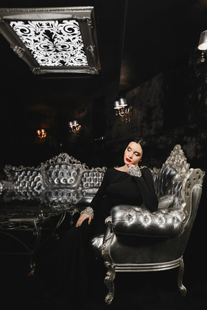 Fashionable and brunette model woman with perfect body and with red lips in black evening dress with sits on the silver sofa at modern luxury interior