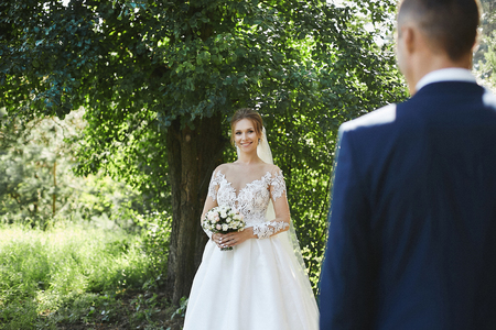 Beautiful young woman with a pretty smile in the stylish wedding dress holding a bouquet of flowers in hands and looking at her groom outdoors