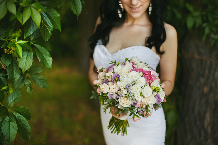 A beautiful flower bouquet of fresh pink and white rose flowers in the hands of sexy brunette beauty in dress. 版權商用圖片