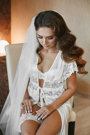 Sexy half-naked brunette model woman with wedding hairstyle and with bright makeup in stylish lace lingerie puts on wedding garter and preparing for a wedding ceremony