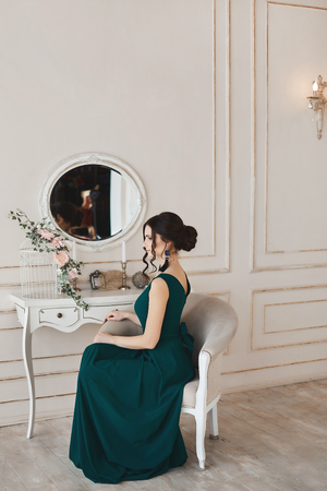 Fashionable young model woman with stylish hairstyle in trendy evening dress sits in the armchair near the dressing table