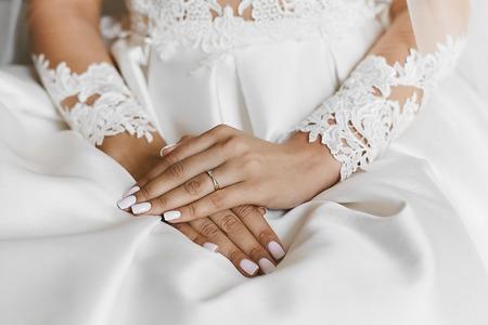 Hermosas manos femeninas con el anillo de bodas y manicura elegante Foto de archivo
