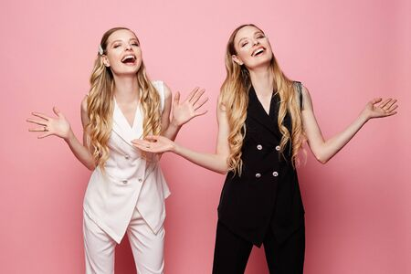 Beautiful, sexy and fashionable twins, two happy and smiling blonde young model girls in sleeveless jackets and pants, isolated at pink background