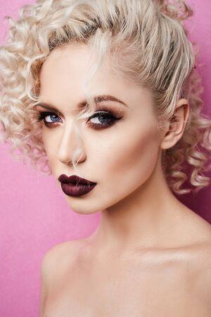 Hermosa mujer joven con labios carnosos y ojos azules aislado en fondo rosa Foto de archivo
