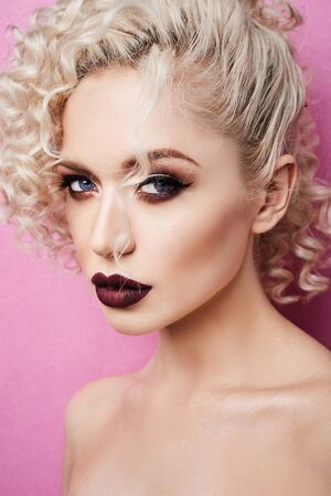 Piękna młoda kobieta z pełnymi ustami i niebieskimi oczami odizolowanymi na różowym tle Zdjęcie Seryjne