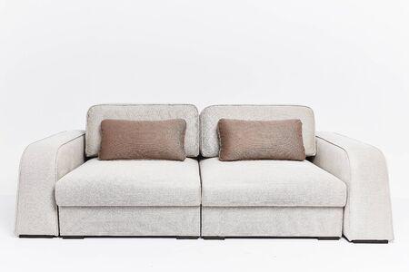 El sofá beige de estilo moderno con dos almohadas marrones aislado sobre fondo blanco. Foto de archivo
