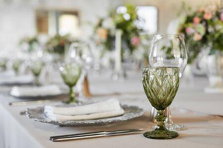 Tisch serviert mit Gläsern, Teller, Gabeln und Messern. Gedienter festlicher Tisch, der für Gäste bereit ist. Luxuriöser Hochzeitstisch