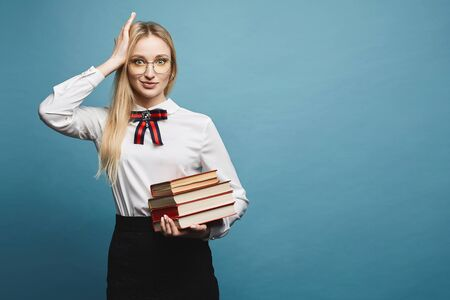 Smart and beautiful blonde model girl in a fashionable blouse and in stylish black skirt holding a stack of various textbooks, isolated at a blue background