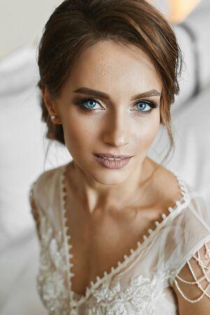 Schöne brünette Frau mit Hochzeitsfrisur, mit hellem Make-up und mit tiefblauen Augen. Porträt der jungen schönen Braut am Morgen