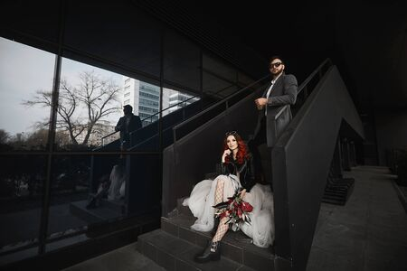 Cool couple posing on stairs near black background Stock Photo