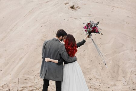 Happy newlyweds posing together in the desert Stock Photo
