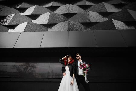 Trendy cool and brutal fiance and fashionable bride posing on the black urban background at the city street Stock Photo