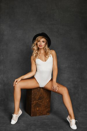 Beautiful and sexy blonde model girl with perfect body in fashionable white bodysuits, trendy black hat and sneakers posing on grey isolated background. Seductive blonde sitting and looking at camera