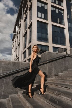 Beautiful, sexy and fashionable blonde girl with perfect body in black evening dress posing at urban background
