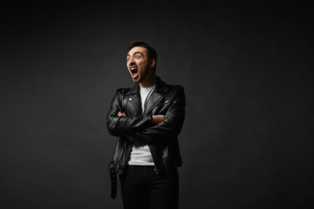 Screaming brutal handsome man in black leather jacket folded ones arms and posing at the dark background, isolate. Face expression. Crazy man with a beard