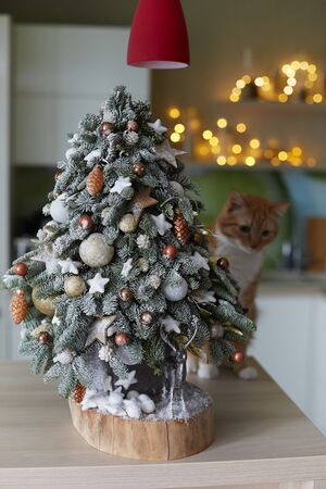 Alternative Christmas tree and small silver deer under it. Small homemade Christmas tree made of fir branches with artificial snow on wooden desk. Concept of New year decoration for holidays