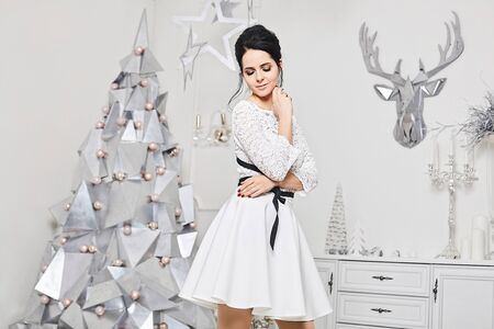 Sexy and beautiful brunette model woman, with perfect body and modish hairstyle, in a fashionable dress posing near silver abstract Christmas tree in the interior decorated for New Year Stock Photo