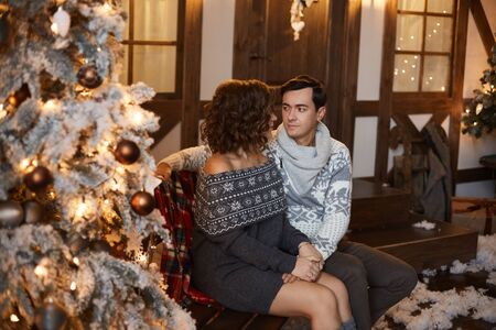 Beautiful couple of lovers in Scandinavian sweaters. Sexy model girl and handsome man looking to each other and posing near Christmas tree. Lovable young woman spending Christmas time with her husband