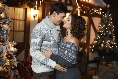 Beautiful couple of lovers in Scandinavian sweaters at New year interior. Sexy model girl and handsome man looking to each other and posing near Christmas tree