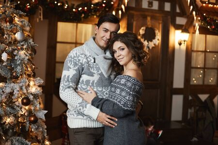 Beautiful couple of lovers in Scandinavian sweaters at New year interior. Sexy model girl and handsome man hugging together. A lovable young woman spending Christmas time with her husband. Stock Photo