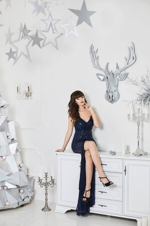 Hot leggy young woman with perfect body in bright evening dress in New year interior. Seductive brunette model girl, with modish hairstyle and sexy legs, sits on the commode Stock Photo