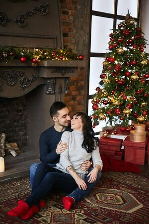 The young happy couple, in warm sweaters and red socks, hugging and sitting on the authentic carpet near the fireplace and Christmas tree. Christmas celebration and New year holidays Stock Photo