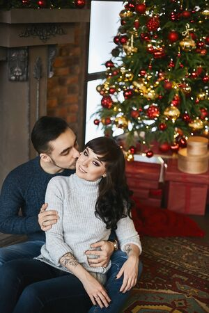 The young happy couple, in warm sweaters. Young handsome man kissing a beautiful girlfriend near the fireplace and Christmas tree in the background. Christmas celebration and New year holidays Stock Photo