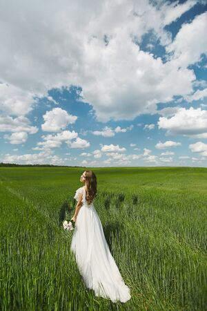Romantic beautiful bride on sunny summer day outdoors. Young blonde woman in a beautiful wedding dress is running across the field. Concept of wedding photoshoot in rustic style Stock Photo