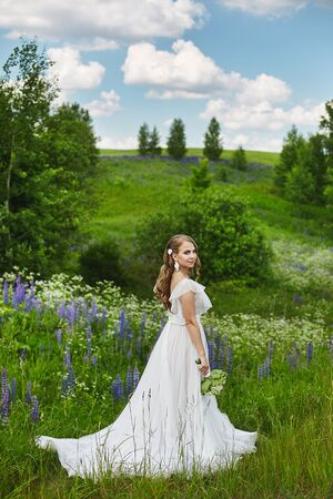 Romantic beautiful bride on sunny summer day outdoors. Young blonde woman in a beautiful wedding dress is posing in blooming field. Concept of wedding photoshoot in rustic style