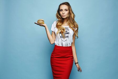 Sexy girl in red skirt and t-shirt holding the double burger and smiling, isolated at a blue background. Portrait of a hungry student girl. Model woman with a perfect body. Concept of fast food Stock Photo
