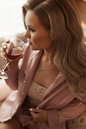 Modish sexy young confident woman, with long platinum blonde hair, in pink silk pajamas sitting in an armchair holding wine glass and drinking. Concept of brides morning before the wedding Stock Photo