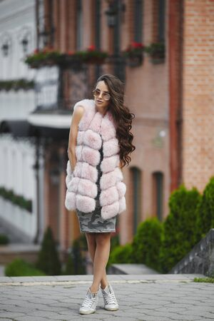A beautiful young woman in camouflage dress and in modish vest from artificial fur posing on the street in spring. Concept of street fashion.