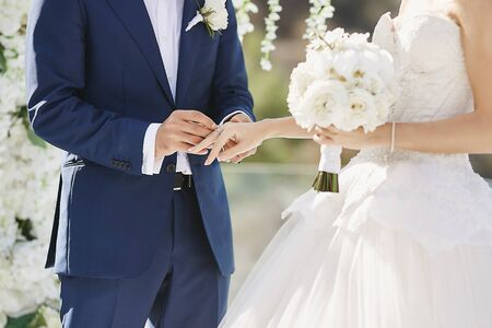 Hands with wedding rings. Modish groom putting a golden ring on the brides finger during the wedding ceremony. Loving couple, a girl in a wedding dress and handsome man in a stylish blue suit