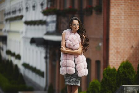Stylish model girl in fashionable fur vest walking across the city street. Concept of street fashion. Stock Photo