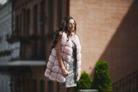 A beautiful young woman in camouflage dress and in modish vest from artificial fur posing on the street in spring. Stylish model girl in fashionable fur vest walking across the city street.