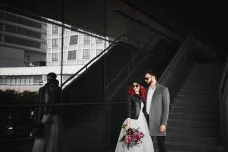 Beautiful couple of lovers posing outdoors during wedding photoshoot. Slim young woman with red hair in modish leather jacket and wedding dress and handsome bearded man in the coat. Stock Photo