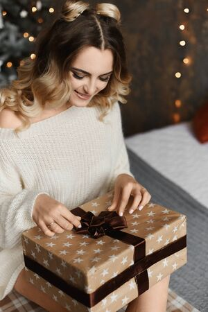 Beautiful model girl with modish hairstyle in oversize sweater sits near Christmas tree with Christmas gift and posing in the interior decorated for New year