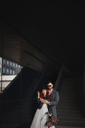 Beautiful couple of lovers hugging outdoors during wedding photoshoot. Slim young woman with red hair in modish leather jacket and wedding dress and handsome bearded man in the coat. Stock Photo