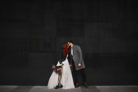 Beautiful couple of lovers kisses outdoors during wedding photoshoot. Slim young woman with red hair in modish leather jacket and wedding dress and handsome bearded man in coat.