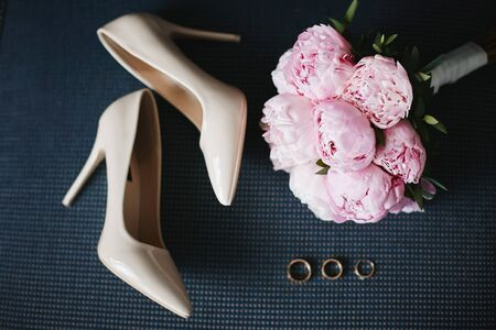 Composition from the bridal bouquet of beautiful pink peonies flowers with a pair of modish bridal shoes and wedding rings. Concept of wedding preparation. Accessories for a bride