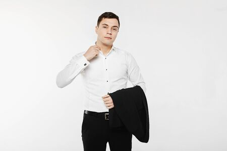 Young businessman wearing in a casual style outfit. The man is posing in a white long sleeve shirt with jeans and holding a jacket on his hand. Concept of mens fashion. Stock Photo